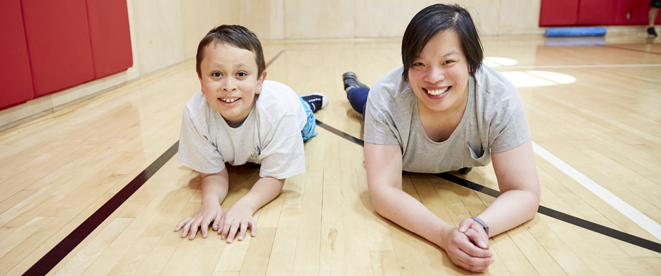 Athlete and volunteer lying on gym floor, hand extended